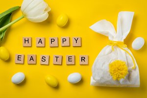 Easter concept - bunny shaped bag with eggs and flowers on bright yellow background,