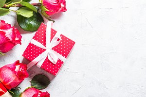 Red rose flower and present box on stone table.