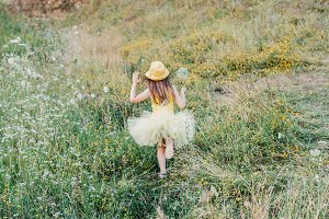 Little girl is playing on the meadow