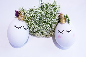 Unicorn eggs hugging a flower