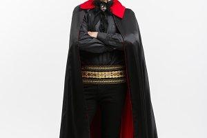 Vampire Halloween Concept - Full lenght Portrait of handsome caucasian Vampire in black and red halloween costume.