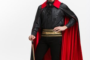 Vampire Halloween Concept - Full lenght Portrait of handsome caucasian Vampire in black and red halloween costume.