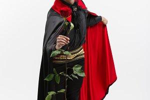Vampire Halloween Concept - Full length Portrait of handsome caucasian Vampire giving red rose.