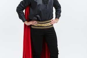 Vampire Halloween Concept - Full length Portrait of handsome caucasian Vampire in black and red halloween costume.