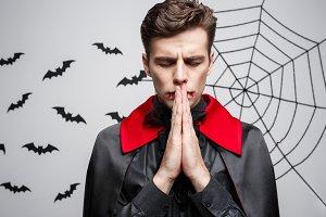 Vampire Halloween Concept - Portrait of handsome caucasian in Vampire halloween costume praying.