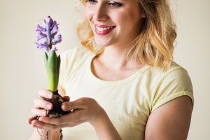 Young woman holding a flower seedling at home.