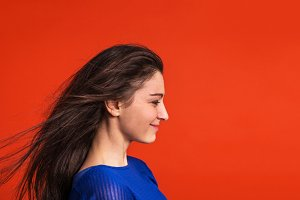 A young woman in studio on a red background.