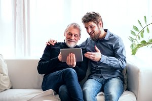 Hipster son and his senior father with tablet at home.