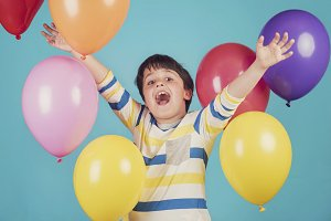 smiling boy with colorful balloons