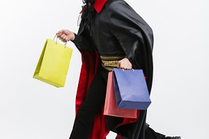 Vampire Halloween Concept - Happy handsome caucasian Vampire holding colorful shopping bag on white background.