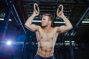 Muscular guy doing exercise on the rings Cross fit style