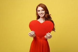 Lifestyle and Holiday Concept - Portrait Young happy red hair woman in orange beautiful dress holding big red heart paper.
