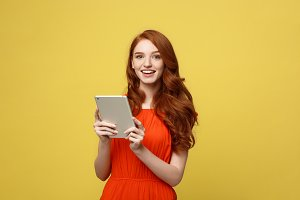 Business Women, Smiling business woman, Business lady, Work concept: Portrait of smiling charming redhead young woman with working on tablet isolated over bright yellow background.