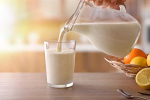 Filling glass of milk with jug