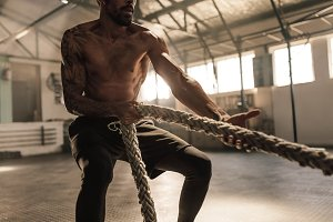 Athlete doing exercises with rope