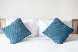 white pillow and blue pillow on bed