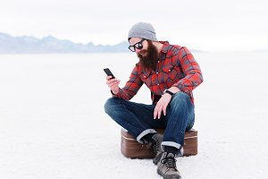 hipster on phone in the salt flats