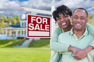 Couple In Front of Home Sale Sign