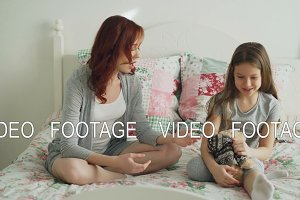 Young careful mother and little cheerful daughter talking and sharing secrets while sitting on bed at home in bedroom. Relationship and family concept