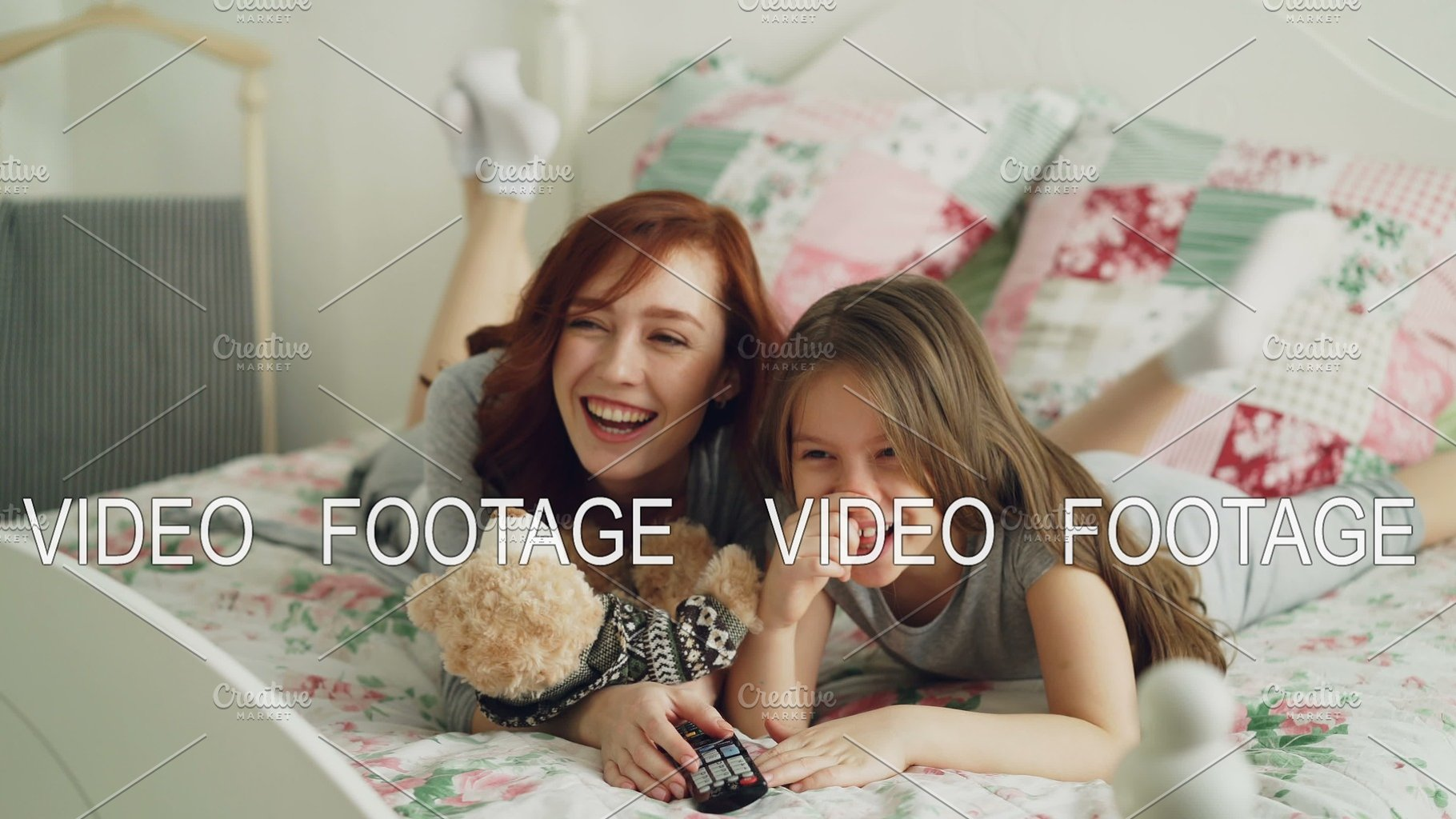 Laughing happy mother and cute daughter watching funny cartoon movie on TV  while lying on bed at home in the morning and have fun