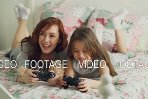 Happy young mother and cute cheerful daughter playing computer console games on TV while lying on bed at home in the morning and have fun