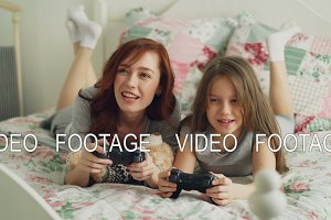 Beautiful happy mother with little daughter laughing and have fun while playing computer console games on TV lying on bed at home in the morning in cozy bedroom