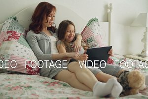 Smiling cute girl and her young mother laughing and watching movie on digital tablet while sitting on bed at home in the morning