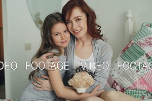 Portrait of adorable smiling girl embracing her happy mother and looking at camera together while sitting on bed in bright bedroom at home