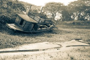 Dried river with old boat on cracked