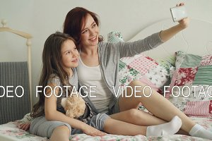 Happy mother and little girl taking selfie photo with smartphone camera and have fun grimacing while sitting in cozy bed at home. Family, people and technology concept