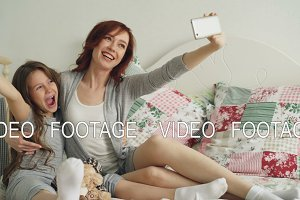 Happy mother and little girl taking selfie photo with smartphone camera and have fun grimacing while sitting in cozy bed at home