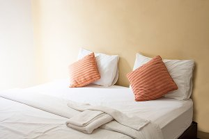 white pillow , orange pillow on bed