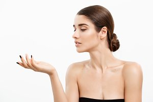 Health care and spa concept - attractive young and healthy woman blowing a kiss from her hand white background.