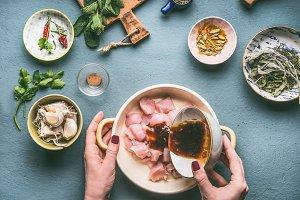 Hands marinates chicken pieces