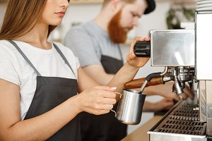 Coffee Business Concept - portrait of lady barista in apron preparing and steaming milk for coffee order with her partner while standing at cafe.