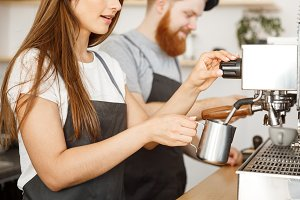 Coffee Business Concept - portrait of lady barista in apron preparing and steaming milk for coffee order with her partner while standing at cafe