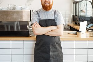 Coffee Business owner Concept - Portrait of happy young bearded caucasian barista in apron with confident looking and smiling to camera in coffee shop counter