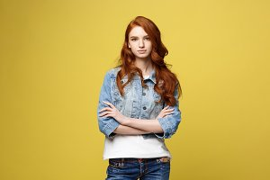 Lifestyle Concept: Young caucasian beautiful woman in denim jacket crossed arms - isolated over bright yellow backgroun