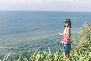Young woman alone on the cliff with beautiful ocean background. Bali island.