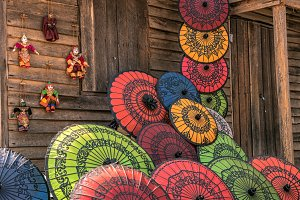 Colorful paper umbrellas on a wooden wall