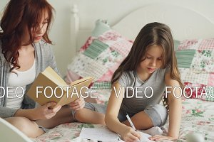 Young mother helps her little cute daughter with homework for elementary school. Loving mom reading a book and girl writing notes in copybook while sitting together on bed at home