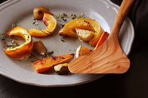 Grilled fall seasonal vegetables on plate over a dark background