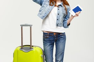 Travel Concept: Portrait of a cheerful young caucasian woman casual dress holding passport with flying tickets while standing with a suitcase and pointing finger away isolated over yellow background.