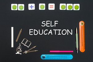 Black art table with stationery supplies with words self education