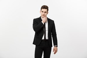 Young handsome man in black suit and glasses looking at copy-space thinking or dreaming isolated over white background