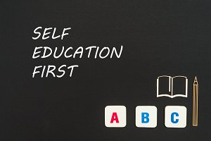 ABC letters and chipboard miniature on blackboard with words self education first