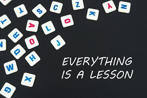 English colored square letters scattered on black background with words everything is a lesson