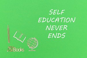 From above wooden minitures school supplies on green background with text self education never ends