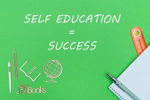 School supplies wooden miniatures and notebook with text self education success on green background