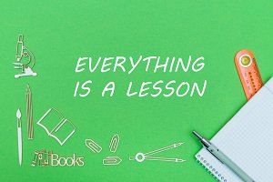School supplies wooden miniatures and notebook with ruler and pen with text everything is lesson on green background